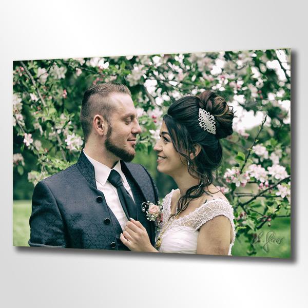 Das Brautpaar im Grünen. Der schönste Tage im Leben extravagant und pompös in Szene gesetzt - blühende Natur und der knisternde Kuss nach der Trauung. Strahlend weisses Hochzeitskleid und eleganter Anzug