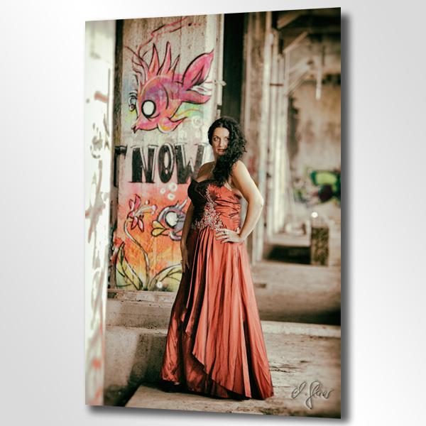 Die elegante Dame mit schwarzem Haar im edelen Abendkleid steht stolz vor ihrer Kulisse. Dieses Foto entstand während einer Fotosession mit Michael Glaser, dem professionellen Fotografen in Krefeld und NRW.