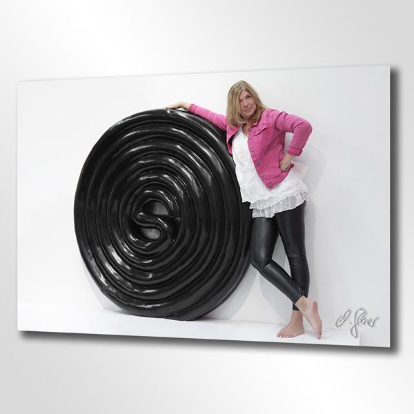 Die große Lakritzschnecke zum Anlehen. Hier steht barfuß eine blonde Frau mit rosa Jacke an der Wand.