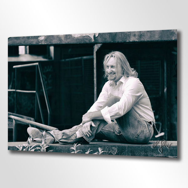 Hier sitzt ein blonder Mann entspannt und gut gelaunt auf einer Mauer, mitten in einer Industrieruine nahe Duisburg. Fotografiert von Michael Glaser.
