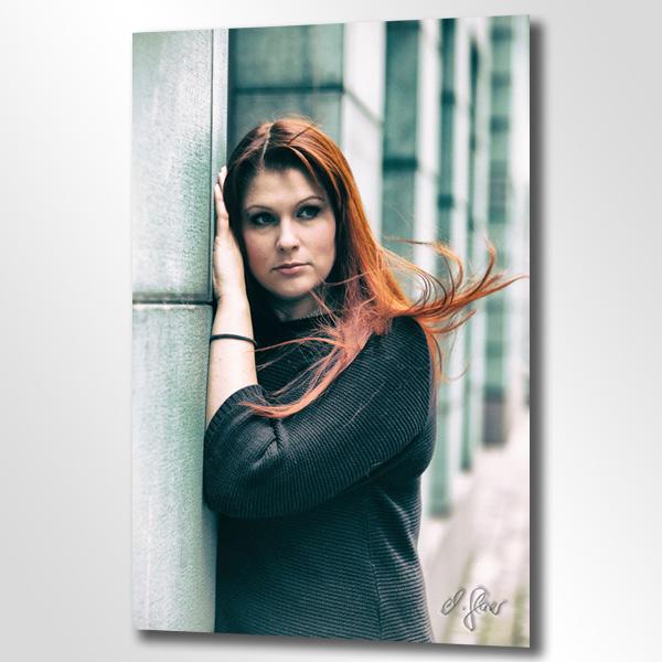 An einer grünen Wand lehnt zart eine Frau mit langen roten Haaren. Der Wind spielt mit ihrer Frisur.
